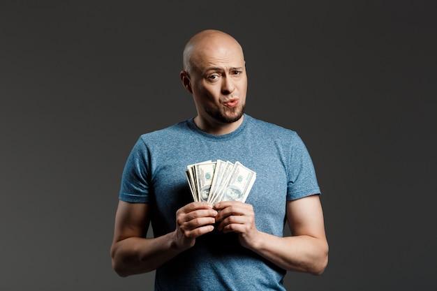 Портрет красивый мужчина в серой рубашке держит деньги на темной стене