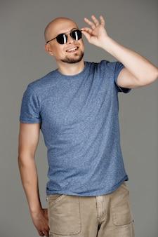 灰色のシャツとサングラスが暗い壁にポーズで自信を持ってハンサムな男の肖像