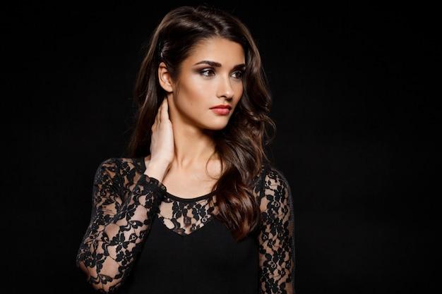 Портрет красивой женщины в черном платье над темной стеной