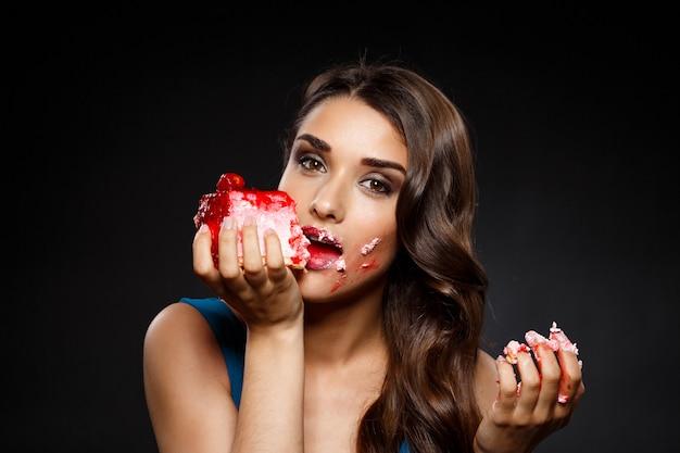 ケーキを食べて青いドレスの陽気な女性