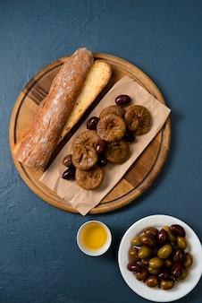 Хлеб, батон, инжир и финики на деревянной доске