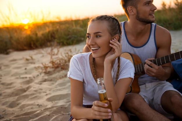 日の出中にビーチで休んで喜んで、友人の若い会社