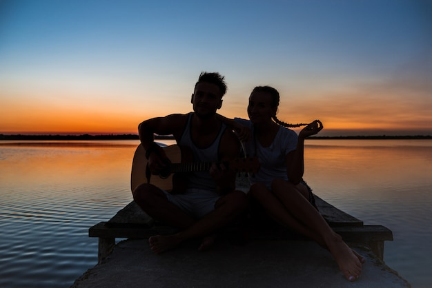 湖の近くの日の出で喜び休んで若い美しいカップルのシルエット