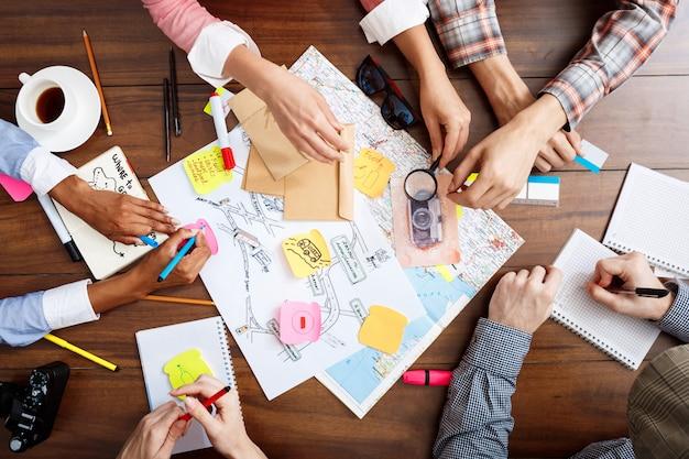 Бизнесмены руки на деревянный стол с документами и проектами