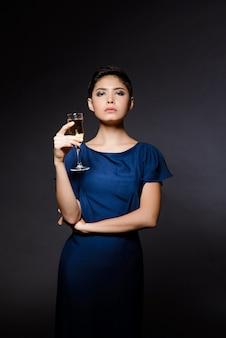 Красивая брюнетка женщина в вечернем платье позирует, держа шампанское стекло