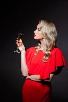 Красивая блондинка в вечернем платье позирует, держа шампанское стекло