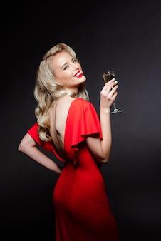 Красивая блондинка в вечернем платье, улыбаясь, держа шампанское стекло