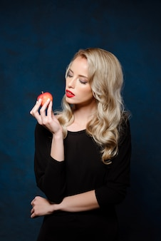リンゴを保持している黒のドレスで明るい化粧品で美しいブロンドの女性