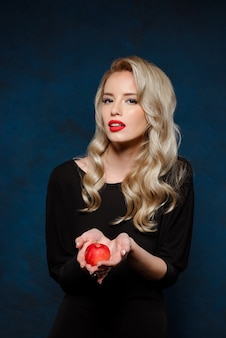 リンゴを保持している黒のドレスで美しいブロンドの女性