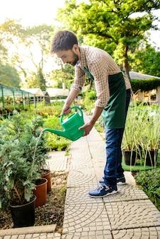 若いハンサムな陽気な庭師笑顔、水遣り、植物の世話