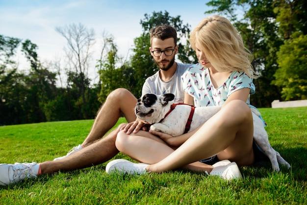 Пара, улыбаясь, сидя на траве с французским бульдогом в парке
