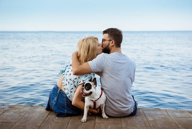 Пара сидит с французским бульдогом у моря