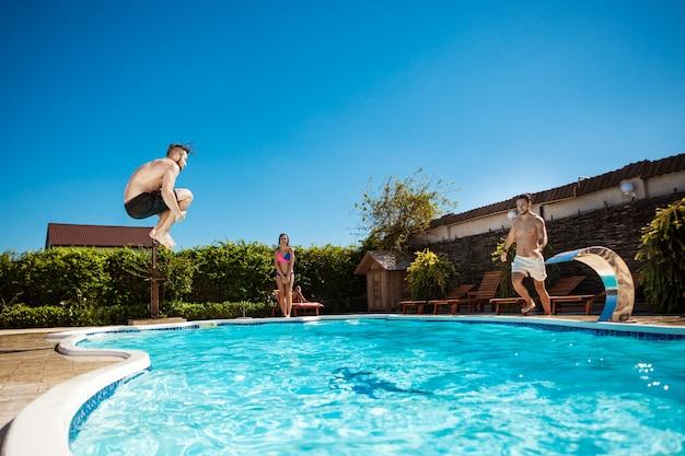 笑顔、リラックス、スイミングプールでジャンプ若い陽気な友人