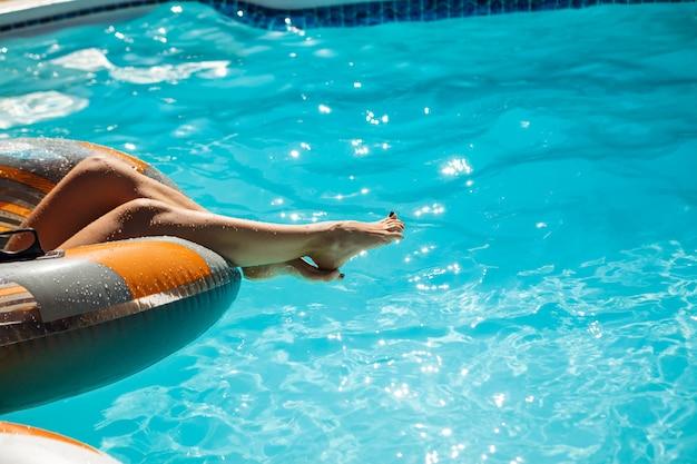 スイミングプールでの女性の足の写真をクローズアップ
