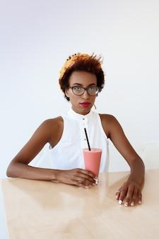 カフェで休んでスムージーを飲むファッション若い美しい女性