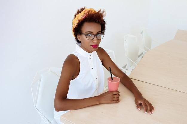 カフェで休んで笑顔スムージーを飲む若い美しい女性