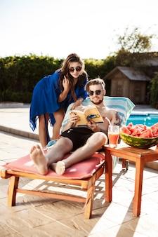 日光浴、本を読んで、スイミングプールのそばに横たわっている友人
