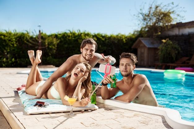 Друзья улыбаются, делают селфи, пьют коктейли, отдыхают возле бассейна