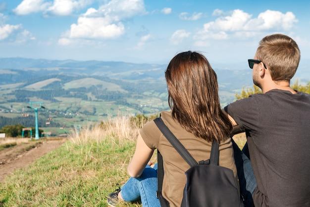 山の風景を楽しんで、丘の上に座っている若いカップル