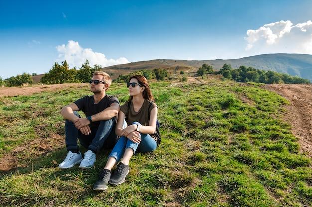 Молодая пара, улыбаясь, наслаждаясь горами пейзаж, сидя на холме