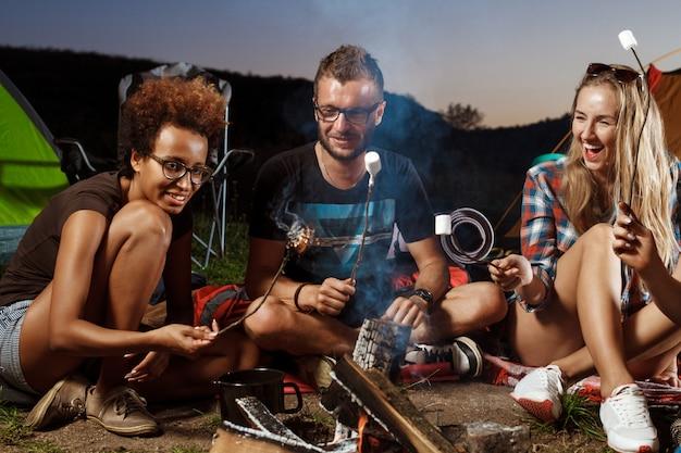 たき火のそばに座って、笑って、ギターを弾いて友達キャンプグリルマシュマロ。