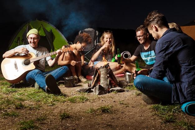 たき火のそばに座って、笑顔で、話して、休んで、ギターを弾く友人
