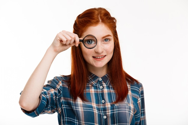 白い壁の上の拡大鏡を持つ美しい生姜少女。