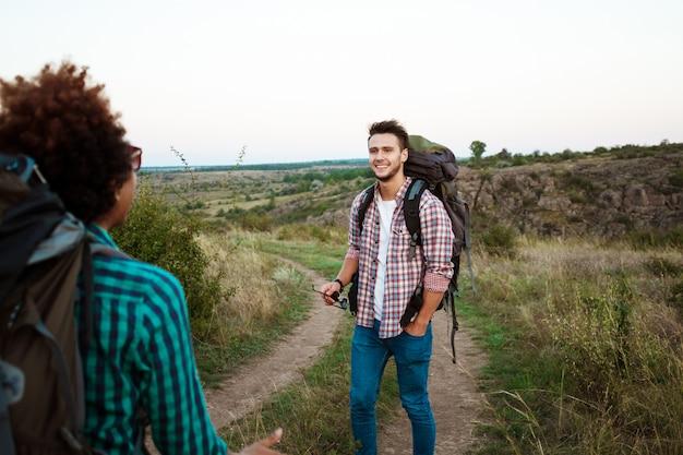 Юные друзья с рюкзаками и хаски улыбаются, путешествуя по каньону