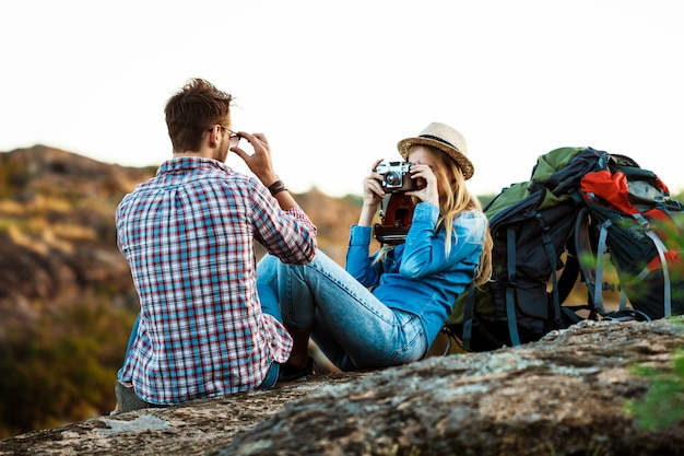 ボーイフレンド、キャニオンの背景の写真を撮る美しい金髪の女性写真家