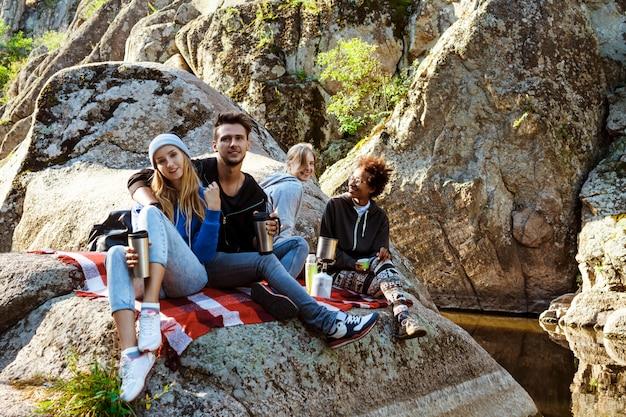 峡谷の岩の上に座って、笑って、お茶を飲む若い友人