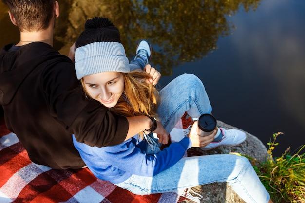 キャニオンの岩の上に座って、笑って、お茶を飲む若いカップル