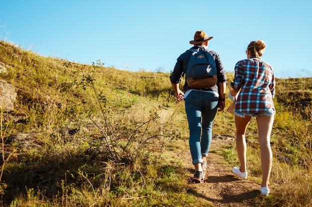 Молодая красивая пара путешественников идет в гору