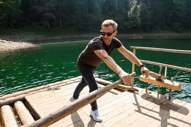 カルパティア山脈の湖でオールを漕いで若いハンサムな男