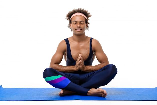 瞑想、ヨガマットの上に座っている陽気な男