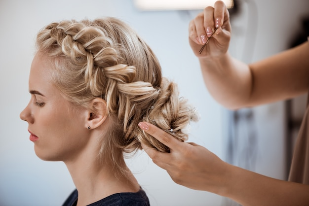 Женский парикмахер делает прическу блондинке в салоне красоты