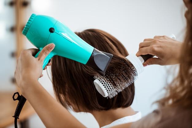 ビューティーサロンでブルネットの女性に髪型を作る女性美容師