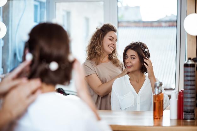 Женский парикмахер и женщина улыбается, глядя в зеркало в салоне красоты