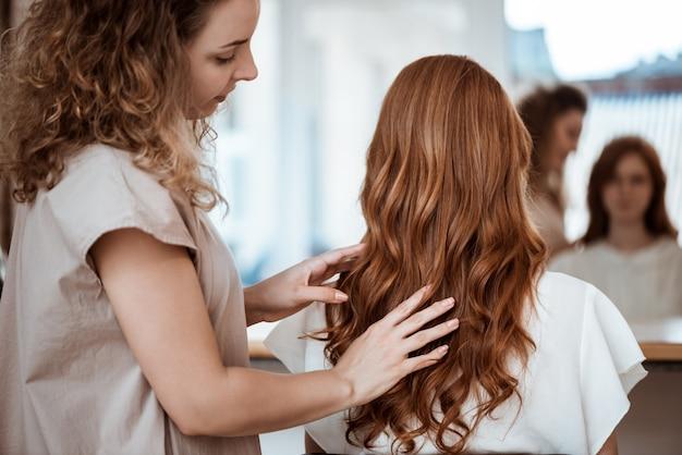 ビューティーサロンで赤毛の女性に髪型を作る女性美容師