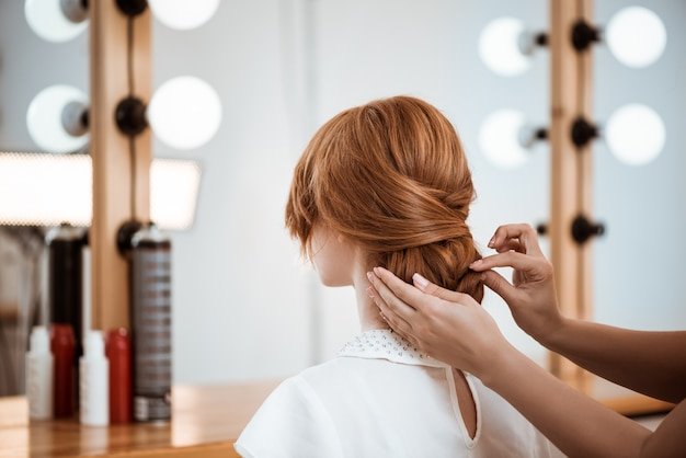 Женский парикмахер делает прическу рыжая женщина в салоне красоты