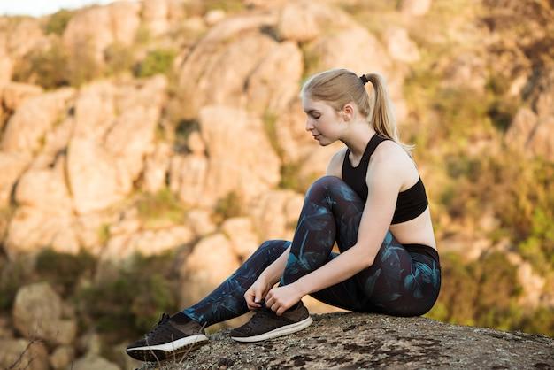 キャニオンの岩の上に座って靴ひもを結ぶ若い陽気な女性