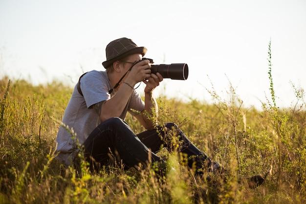 帽子の写真を撮って、フィールドに座っている若い男性カメラマン