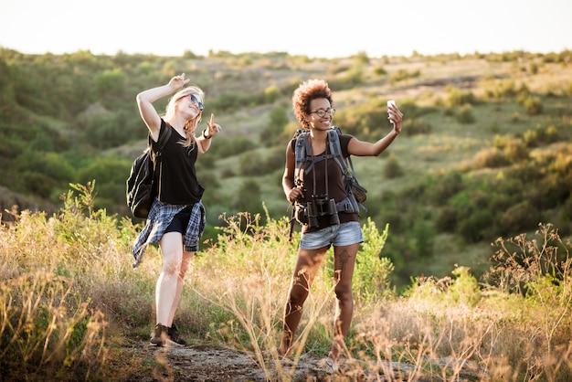 Девушки с рюкзаками улыбаются, делают селфи, путешествуют по каньону