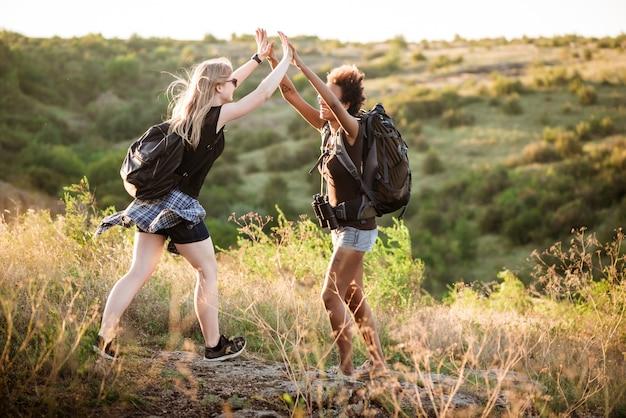Девушки с рюкзаками улыбаются, дают хай-фив, путешествуют в каньоне