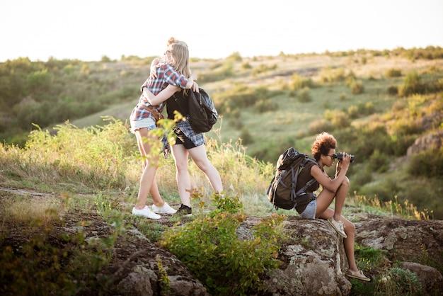 Девушки улыбаются, обнимаются, сидят на скале, наслаждаясь видом в каньоне