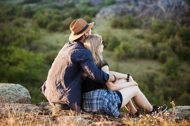 キャニオンの眺めを楽しみながら休んで若い美しいカップル
