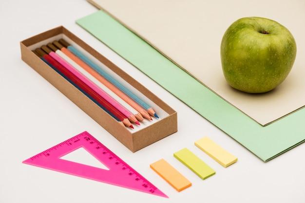 学用品と白いテーブルの上のリンゴ