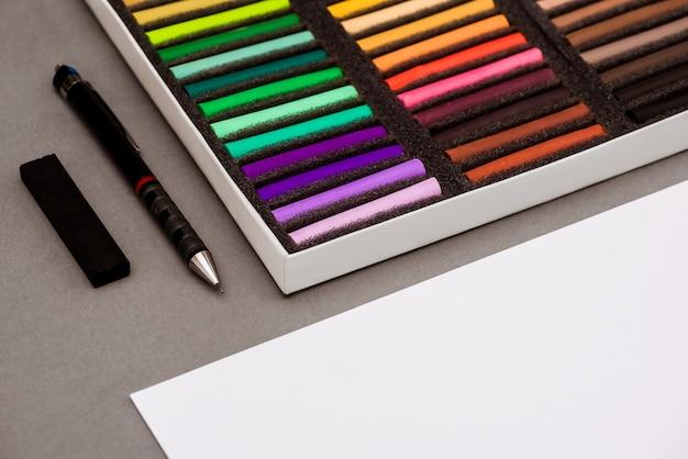 カラフルなパステル、ペン、灰色のテーブルの上の紙