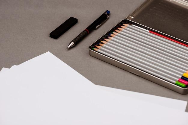 カラフルな鉛筆、ペン、灰色のテーブル上の紙