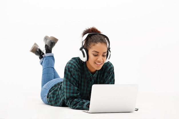 Портрет молодой африканской женщины с ноутбуком на белом