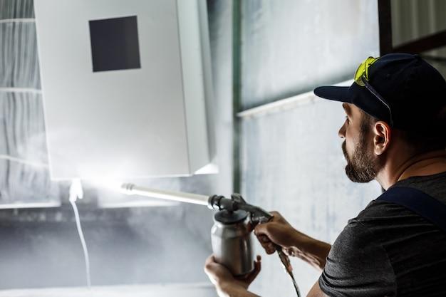 Рабочий красит деталь пневматическим пистолетом.